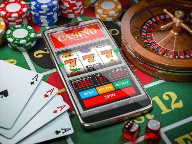 mobiele telefoon, gokautomaat, dobbelstenen, kaarten en roulette op een groene tafel in casino | gokkasten